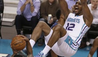 Charlotte Hornets' Dwight Howard (12) dunks over Minnesota Timberwolves' Jeff Teague (0) during the second half of an NBA basketball game in Charlotte, N.C., Monday, Nov. 20, 2017. (AP Photo/Chuck Burton)