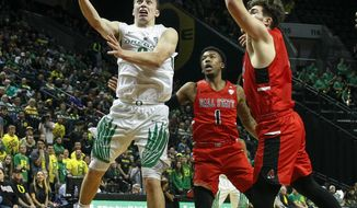 Oregon guard Payton Pritchard drives past Ball State guard Jontrell Walker (1) and Ball State guard Tayler Persons during the second half of their NCAA college basketball game at Matthew Knight Arena, Sunday, Nov. 19, 2017. (Andy Nelson/The Register-Guard via AP)