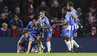 Brighton's Pascal Gross on ground, celebrates scoring his side's first goal of the game with teammates, during the English Premier League soccer match between Brighton and Stoke City, at the AMEX Stadium, in Brighton, England, Monday, Nov. 20, 2017. (Gareth Fuller/PA via AP)