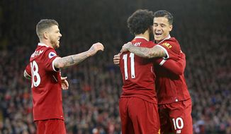 Liverpool's Mohamed Salah celebrates scoring his side's second goal of the game with team mates Liverpool's Philippe Coutinho, right, and Alberto Moreno left, during the English Premier League soccer match Liverpool versus Southampton at Anfield, Liverpool, England, Saturday Nov. 18, 2017. (Peter Byrne/PA via AP)