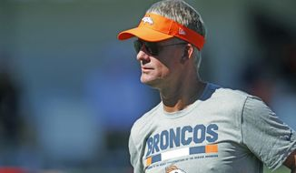 FILE - In this Thursday, July 27, 2017, file photo, Denver Broncos offensive coordinator Mike McCoy takes part in drills during an NFL football training camp in Englewood, Colo. The Broncos, who have lot six straight games for the first time in 27 seasons, announced that McCoy had ben fired Monday, Nov. 20, and replaced by quarterbacks coach Bill Musgrave. (AP Photo/David Zalubowski, File)