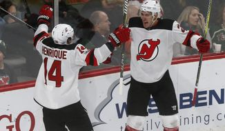 New Jersey Devils' John Moore, right, and Adam Henrique celebrate Moore's winning goal in overtime off Minnesota Wild goalie Devan Dubnyk in an NHL hockey game Monday, Nov. 20, 2017, in St. Paul, Minn. The Devils won 4-3. (AP Photo/Jim Mone)
