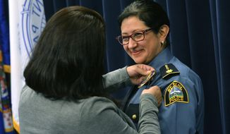In a Monday, Nov. 13, 2017 photo, the commander's badge is pinned onto Pamela Barragan by her sister Erika, during a ceremony at the St. Paul Police Western District Headquarters in St. Paul, as she is promoted to Commander in the St. Paul Police Department. Barragan becomes the first Latina commander in the history of the department. (Scott Takushi/Pioneer Press via AP)