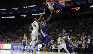 Philadelphia 76ers' Joel Embiid (21) goes up for a shot against Utah Jazz's Derrick Favors (15) during the first half of an NBA basketball game, Monday, Nov. 20, 2017, in Philadelphia. (AP Photo/Matt Slocum)