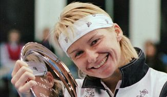 In this Nov. 17, 1996, file photo, Jana Novotna, of the Czech Republic, is all smiles after taking home a $79,000 check from the Advanta Tennis Championship in Villanova, Pa. The WTA says the 1998 Wimbledon champion Jana Novotna of the Czech Republic has died. In a Monday, Nov. 20, 2017, statement, the WTA say Novotna died after battling a cancer on Sunday, Nov. 19. She was 49. (AP Photo/Jim Graham, File)