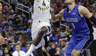 Indiana Pacers' Victor Oladipo (4) goes past Orlando Magic's Nikola Vucevic (9) for a basket during the first half of an NBA basketball game, Monday, Nov. 20, 2017, in Orlando, Fla. (AP Photo/John Raoux)