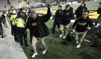 Purdue head coach Jeff Brohm, left, waves to fans as he runs off the field after an NCAA college football game against Iowa, Saturday, Nov. 18, 2017, in Iowa City, Iowa. Purdue won 24-15. (AP Photo/Charlie Neibergall)