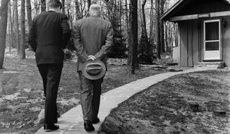 President John F. Kennedy, left, walking a path at Camp David with Dwight D. Eisenhower on April 22, 1961. The two met to discuss the Bay of Pigs invasion. Associated Press/Paul Vathis)