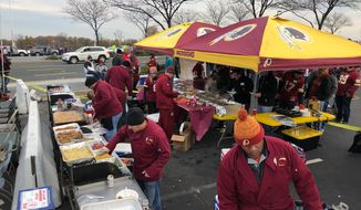 """""""Hail BBQ,"""" a group of avid Redskins tailgaters, prepare food Nov. 12 before Washington's game against the Minnesota Vikings in the parking lot of FedEx Field. (Photo courtesy of Ted Abela.)"""