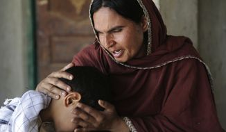 Kausar Parveen comforts her child, who said he was raped by a mullah or religious cleric, in Kehror Pakka, Pakistan. Sexual abuse is a pervasive and long-standing problem at Pakistan's network of Islamic schools known as madrassas, an Associated Press investigation has found.  (Associated Press)