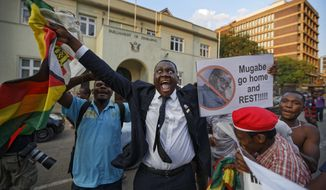 Zimbabweans celebrate outside the parliament building immediately after hearing the news that President Robert Mugabe had resigned, in downtown Harare, Zimbabwe Tuesday, Nov. 21, 2017. Mugabe resigned as president with immediate effect Tuesday after 37 years in power, shortly after parliament began impeachment proceedings against him. (AP Photo/Ben Curtis)