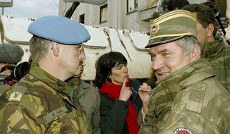FILE - In this April 9, 1994 file photo, former Bosnian Serb commander Ratko Mladic, right, leaves the UN headquarters at Sarajevo airport after talks with the UN General, Sir Michael Rose and Bosnian Commander Rasim Delic. Ratko Mladic will learn his fate on Nov. 22, 2017, when U.N. judges deliver verdicts in his genocide and war crimes trial. (AP Photo/Enric Marti, File)