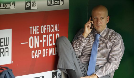 FILE-This Sept. 4, 2015, file photo shows Atlanta Braves assistant general manager and director of pro scouting John Coppolella talking on the phone in the dugout during batting practice before a baseball game against the Washington Nationals at Nationals Park, in Washington. Baseball Commissioner Rob Manfred has hit the Atlanta Braves with heavy sanctions, including the loss of nine players, for rules violations committed by the team in the international player market. Manfred on Tuesday, Nov. 21, 2017,  also placed former Braves general manager Coppolella on the permanently ineligible list. Former Braves Special Assistant Gordon Blakeley, the team's international scouting chief, is suspended from performing services for any team for one year. (AP Photo/Alex Brandon, File) **FILE**