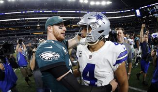 Philadelphia Eagles' Carson Wentz, left, and Dallas Cowboys' Dak Prescott, right, greet each other after their NFL football game, Sunday, Nov. 19, 2017, in Arlington, Texas. (AP Photo/Ron Jenkins)