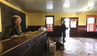 ADVANCE FOR WEEKEND EDITIONS, NOV. 25-27 - In this Nov. 9, 2017 photo, Barbara Lund, a third generation member of the family-owned Wittnebel's Tavern in Old Ashippun, Wis., spends a few final moments with the former business' historic bar which is being donated to the Wisconsin Historical Society. (John Hart/Wisconsin State Journal via AP)