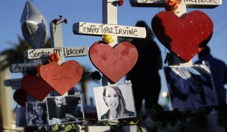 FILE - In this Oct. 6, 2017, file photo, a woman passes crosses for victims of the mass shooting in Las Vegas. Millions of dollars in donations have poured in for the victims of the mass shooting at a Las Vegas country music festival, leaving local officials and national experts to sort how to fairly and quickly distribute the money. (AP Photo/Gregory Bull, File)