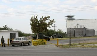 FILE - In this Sept. 18, 2012 file photo, Mexican army soldiers guard an entrance to the state prison in Piedras Negras, Mexico. Officially it was a prison, but inside it hid another reality: a center of operations where the Zetas cartel modified vehicles and manufactured uniforms, locked up kidnap victims and dissolved bodies in acid, according to a College of Mexico report released Tuesday, Nov. 21, 2017, based on witness statements, documents and public data. (AP Photo/Adriana Alvarado, File)