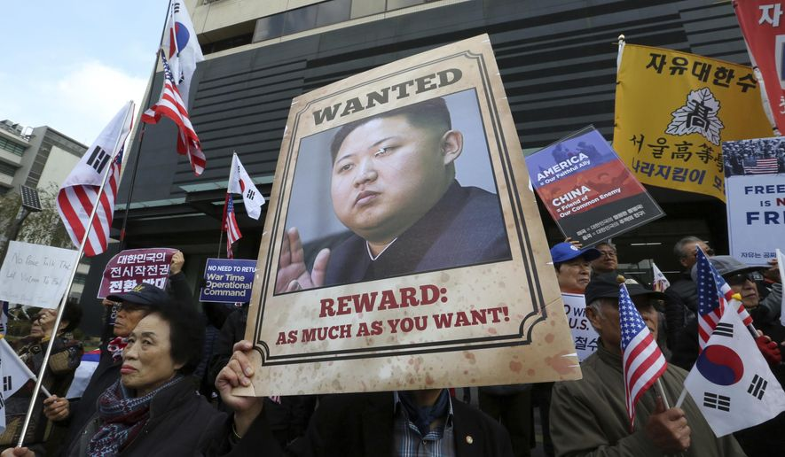 FILE - In this Monday, Nov. 6, 2017, file photo, an anti-North Korea protester holds up a portrait of North Korean leader Kim Jong Un during a rally welcoming the visit by U.S. President Donald Trump near the U.S. Embassy in Seoul, South Korea.North Korea is on its way back onto a very short list of countries the United States says sponsor terrorism. The designation will expand the already substantial array of sanctions the U.S. has imposed on trade with North Korea. (AP Photo/Ahn Young-joon, File)