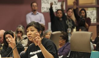 Ahjani Yepa, a Jemez Pueblo member, testifies in opposition of a proposed ordinance that would govern oil and gas development in Sandoval County as others raise their fists in solidarity during a County Commission meeting in Bernalillo, N.M., on Thursday, Nov. 16, 2017. Critics of the ordinance say it does not go far enough to protect groundwater resources. (AP Photo/Susan Montoya Bryan)