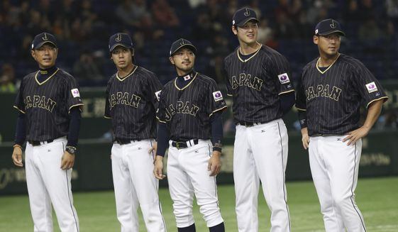 FILE- THIS Nov. 11, 2016, file photo shows Team Japan, from left, manager Hiroki Kokubo, infielder Tetsuto Yamada, infielder Ryosuke Kikuchi and designated hitter Shohei Ohtani and infielder Sho Nakata standing during a ceremony prior to their international exhibition series baseball game against Mexico at Tokyo Dome in Tokyo. A person familiar with the agreement tells The Associated Press that Major League Baseball, its Japanese counterpart and the American players' union agreed Tuesday, Nov. 21, 2017,  to a new posting system that could allow Japanese star pitcher-outfielder Shohei Ohtani to be put up for bid next week.  (AP Photo/Koji Sasahara, File) **FILE**