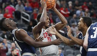 UNLV's Shakur Juiston, center, grabs a rebound over Rice's Robert Martin, left, and Connor Cashaw during the first half of an NCAA college basketball game Monday, Nov. 20, 2017, in Las Vegas. (AP Photo/John Locher)