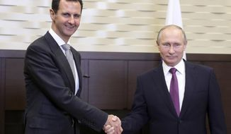 In this photo taken on Monday, Nov. 20, 2017, Russian President Vladimir Putin, right, shakes hand with Syrian President Bashar Assad in the Bocharov Ruchei residence in the Black Sea resort of Sochi, Russia. Russian state TV said the two leaders held bilateral talks on Monday and then met with Russian military chiefs. It was the second time Assad has traveled to Russia to meet with Putin in the course of the country's six-year civil war.  (Mikhail Klimentyev, Kremlin Pool Photo via AP)