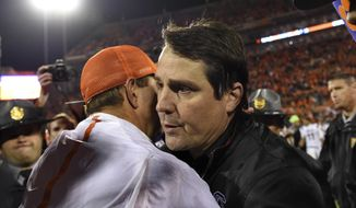"FILE - In this Nov. 26, 2016, file photo, Clemson head coach Dabo Swinney, left, and South Carolina head coach Will Muschamp meet at midfield after an NCAA college football game against in Clemson, S.C. Clemson won 56-7. South Carolina's mission is as clear as it's motto this week: ""Never again."" Shortly after their embarrassing, 56-7 loss to rival Clemson last year, Gamecocks players vowed they would never again feel that beaten down by its rival.(AP Photo/Richard Shiro, File)"