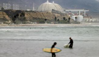 FILE - In this June 7, 2013, file photo, surfers pass in front of the San Onofre nuclear power plant in San Onofre, Calif. A report says California Public Utilities Commission lawyers sought to suppress court-approved search warrants after utility regulators promised they would cooperate with a state criminal investigation. Court documents unsealed Monday, Nov. 20 2017, show commission lawyers opposed providing records to investigators as required by three different warrants approved in 2015 and 2016.  (AP Photo/Gregory Bull, File)