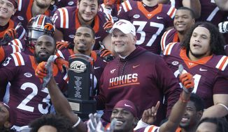 FILE - In this Saturday Nov. 26, 2016, file photo, Virginia Tech head coach Justin Fuente and his team celebrate their 52-10 win over Virginia after an NCAA college football game in Blacksburg, Va. The No. 24 Hokies have won 13 in a row in the series, and pledge to go into Friday night's matchup at Scott Stadium determined not to be the team to let their program's dominance of the Cavaliers come to an end. (AP Photo/Steve Helber, File)