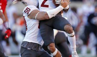 Washington State's Hercules Mata'afa (50) lifts Robert Taylor (2) after his interception against Utah in the first half of an NCAA college football game, Saturday, Nov. 11, 2017, in Salt Lake City. (AP Photo/Rick Bowmer)