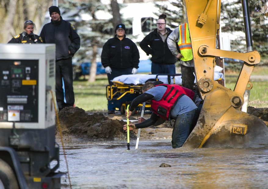 Emergency crews attempt to save a construction worker who became trapped in a flooded hole after a water main broke in Burton, Mich., on Tuesday, Nov. 21, 2017. The man, who was trapped underwater for roughly 20 minutes, did not have a pulse when he was taken to the hospital but medical personnel were able to re-establish a heartbeat, according to Burton police Chief Tom Osterholzer. He is listed in extremely critical condition. (Terray Sylvester/MLive.com via AP)