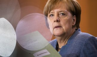 In this photo taken with light reflections on a pot German Chancellor Angela Merkel attends the weekly cabinet meeting of the German government at the chancellery in Berlin, Wednesday, Nov. 22, 2017. (AP Photo/Markus Schreiber)