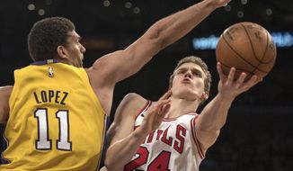Chicago Bulls forward Lauri Markkanen, right, shoots under pressure as Los Angeles Lakers center Brook Lopez defends him during the first half of an NBA basketball game Tuesday, Nov. 21, 2017, in Los Angeles. (AP Photo/Kyusung Gong)