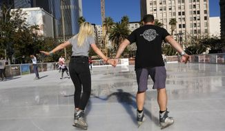 A couple carefully maneuver their way around the Holiday Ice Rink in Pershing Square in downtown Los Angeles on Wednesday, Nov. 22, 2017. A large swath of California is sweating in a Thanksgiving week heat wave. Temperatures warmed up quickly Wednesday and were well into the 90s in many areas by early afternoon. (AP Photo/Richard Vogel)