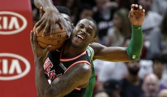 Miami Heat's Dion Waiters fights for the ball with Boston Celtics' Jaylen Brown during the first half of an NBA basketball game, Wednesday, Nov. 22, 2017, in Miami. (AP Photo/Lynne Sladky)