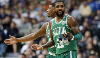 Boston Celtics' Marcus Smart, rear, escorts Kyrie Irving, front, away after Irving was charged with a technical foul in the second half of an NBA basketball game against the Dallas Mavericks on Monday, Nov. 20, 2017, in Dallas. (AP Photo/Tony Gutierrez)