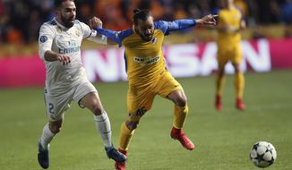 Real Madrid's Daniel Carvajal, left, APOEL's Efstathios Aloneftis challenge for the ball during the Champions League Group H soccer match between APOEL Nicosia and Real Madrid at GSP stadium, in Nicosia, on Tuesday, Nov. 21, 2017. (AP Photo/Petros Karadjias)