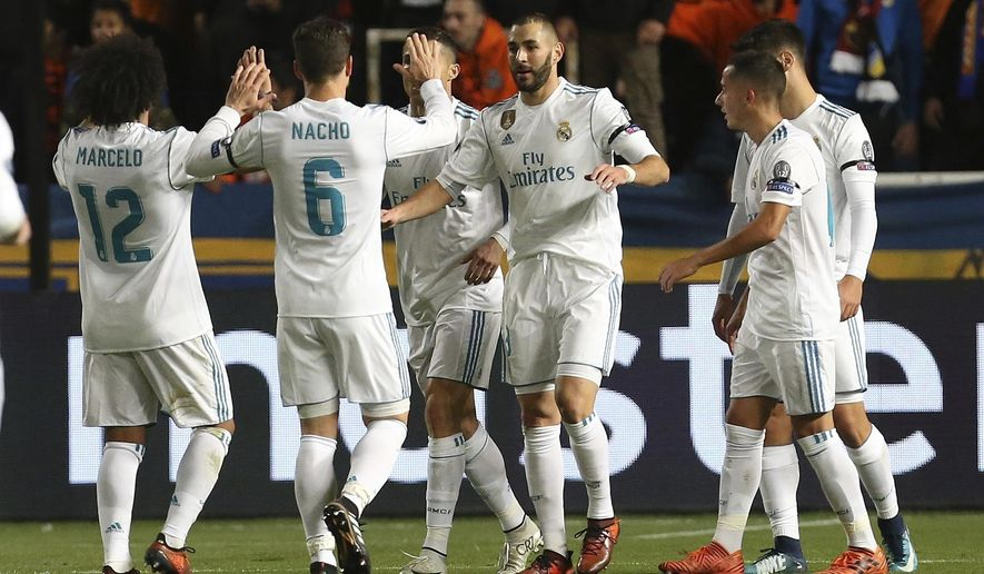 Real Madrid's Karim Benzema, center, celebrates after scoring the fourth goal of his team during the Champions League Group H soccer match between APOEL Nicosia and Real Madrid at GSP stadium, in Nicosia, on Tuesday, Nov. 21, 2017. (AP Photo/Petros Karadjias)