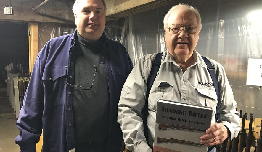 "In this Nov. 16, 2017 photo, Robert Simpson, right, and his son Brad, owners of Simpson Ltd., a  collector gun shop in Galesburg, Ill., pose with the book they respectively compiled and published, ""Training Rifles of Third Reich Germany."" Besides being a book for gun collectors, the book contains original research about a program the Nazis started after Hitler came to power to train German men for war.(Rebecca Susmarski/The Register-Mail, via AP)/"
