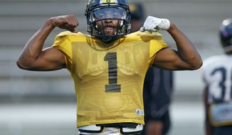 "Grambling's senior quarterback Devante Kincade strikes a ""muscleman"" pose on the sidelines while waiting for his turn to run plays during practice, Thursday, Nov. 16, 2017, at Eddie G. Robinson Memorial Stadium in Grambling, La. Kincade, who played two seasons at Ole Miss, says playing football at a Historically Black College or University is an experience to savor. Playing at an HBCU is not just about entertaining halftime shows the schools are known for, it's about community. (AP Photo/Rogelio V. Solis)"