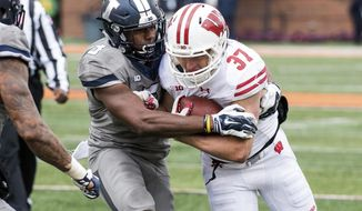 FILE - In this Oct. 28, 2017, file photo, Illinois linebacker Del'Shawn Phillips (3) tries to tackle Wisconsin running back Garrett Groshek (37) during the fourth quarter of an NCAA college football game, Saturday, at Memorial Stadium in Champaign, Ill. Phillips, who spent the past two seasons at a community college in Kansas after academics derailed his college plans out of high school in Detroit, is leading Illinois in tackles in his first season.  (AP Photo/Bradley Leeb, File)