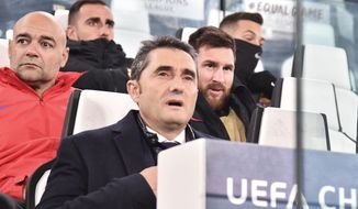 Barcelona coach Ernesto Valverde, foreground, and forward Lionel Messi sit on the bench during the Champions League group D soccer match between Juventus and Barcelona, at the Allianz Stadium in Turin, Italy, Wednesday, Nov. 22, 2017.  (Andrea Di Marco/ANSA via AP)