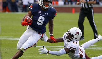 Auburn running back Kam Martin (9) gets around Louisiana Monroe cornerback Corey Straughter (21) as he carries the ball during the second half of an NCAA college football game, Saturday, Nov. 18, 2017, in Auburn, Ala. (AP Photo/Butch Dill)