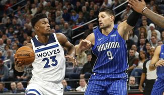 Minnesota Timberwolves' Jimmy Butler, left, eyes the basket as Orlando Magic's Nikola Vucevic of Montenegro defends in the first half of an NBA basketball game Wednesday, Nov. 22, 2017, in Minneapolis. (AP Photo/Jim Mone)