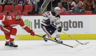 Edmonton Oilers center Connor McDavid (97) controls the puck as he skates by Detroit Red Wings defenseman Mike Green (25) during the first period of an NHL hockey game, Wednesday, Nov. 22, 2017, in Detroit. (AP Photo/Carlos Osorio)