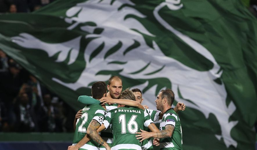 Sporting's Bas Dost, 2nd left, celebrates with team mates after scoring his side's opening goal during a Champions League, Group D soccer match between Sporting CP and Olympiakos at the Alvalade stadium in Lisbon, Wednesday Nov. 22, 2017. (AP Photo/Armando Franca)