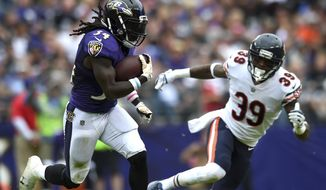 FILE - In this Oct. 15, 2017, file photo, Baltimore Ravens running back Alex Collins, left, rushes past Chicago Bears free safety Eddie Jackson in the first half of an NFL football game in Baltimore. The focal point of the Ravens flourishing running game is Collins, which is no small surprise considering he came off the practice squad in September and fumbled in two of his first three games. (AP Photo/Gail Burton, File)