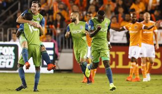 Seattle Sounders defender Gustav Svensson (4) and defender Kelvin Leerdam (18) celebrate Svensson's goal against the Houston Dynamo during the first half of an MLS soccer match in the first leg of the Western Conference championship in Houston on Tuesday, Nov. 21, 2017. Seattle won, 2-0. (Brett Coomer/Houston Chronicle via AP)