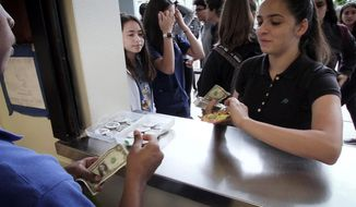 In this Nov. 14, 2017 photo, Danny Vaca-Figuereo, left, collects money from a customer at the Falcon gift shop at John A. Ferguson High School, in Miami. For teenagers with special needs, finding a job after high school can be a challenge. One Miami teacher aims to change that. Ivette Amador has created a gift shop at John A. Ferguson High that's run entirely by special needs students. The teens make all the major business decisions, calculate profits, and run the day to day operations including inventory, sales and stocking shelves. (Jose A. Iglesias/Miami Herald via AP)