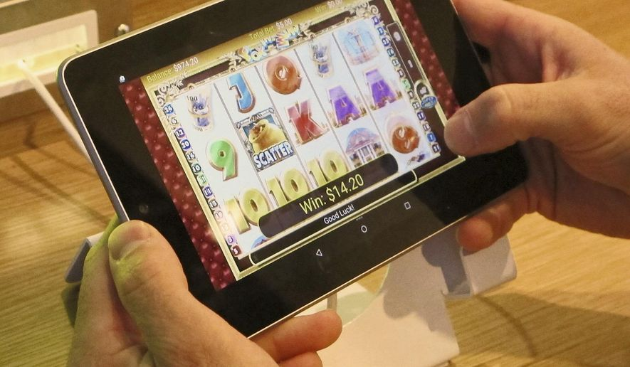 In this April 15, 2015, file photo, an employee at Resorts Casino Hotel tries a touchscreen tablet device the day before the opening of the casino's internet gambling lounge in Atlantic City, N.J. (AP Photo/Wayne Parry, File)